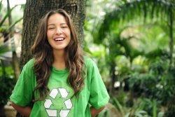 Eine Jugendliche lehnt lachend an einem Baum, Sie trägt ein T-Shirt mit dem Recycling-Symbol