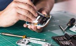 Ein Mann hält ein auseinandergebautes Smartphone in der Hand, um es zu reparieren.