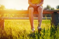 Barfüßiger Junge sitzt im Sonnenlicht auf einer Bank.