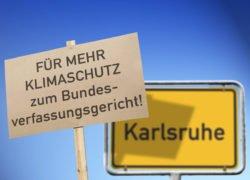 Symbolbild für Klimaklagen: Protestschild vor dem Karlsruher Ortsschild